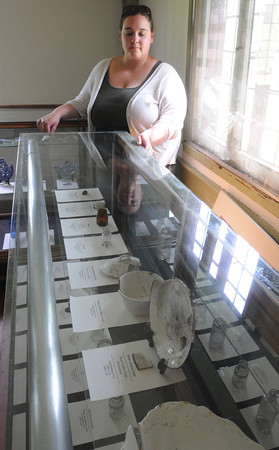 Danvers:<br /> Resident caretaker Candice Clemenzi stands near a display case of mostly 1900' artifacts which is part of the grand opening of the Rebecca Nurse Homestead archaeology exhibit.<br /> Photo by Ken Yuszkus, Salem News, Thursday May 30, 2013.