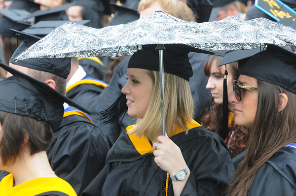 Beverly:<br /> Graduate Stephanie Blanchette of Rhode Island shields herself and Magaret Bolt, right, of Beverly from a rain shower with an umbrella during Endicott College's graduation ceremony. <br /> Photo by Ken Yuszkus/Salem News, Friday May 24, 2013.