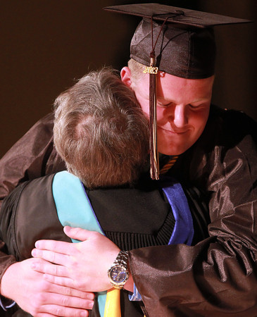 Peabody: Bishop Fenwick graduate Pat Corcoran gives a big hug to Principal Sister Catherine Fleming before receiving his diploma on Friday evening. David Le/Salem News