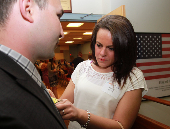 Salem: Ashley Gaffney, of Salem, pins a boutonnière on Jeffrey Maniscalco's jacket prior to the start of a ceremony to give out a veteran's stoll for each veteran graduating from Salem State on Wednesday evening. David Le/Staff Photo