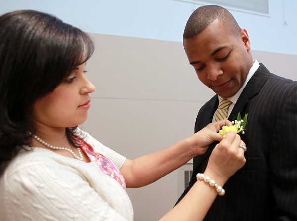 Salem: Karen Machado, of Lynn, pins a boutonnière on her husband Joel's jacket prior to the start of a ceremony to give out a veteran's stoll for each veteran graduating from Salem State on Wednesday evening. David Le/Staff Photo