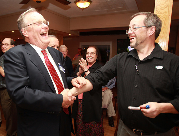 Danvers: Newly elected Danvers Selectman David Mills, left, shakes hands with sitting Selectman Gardner Trask, right, after looking at the preliminary precinct numbers on Tuesday evening. Mills and re-elected Selectman Dan Bennett claimed the two available seats, beating out Keith Lucy. David Le/Staff Photo