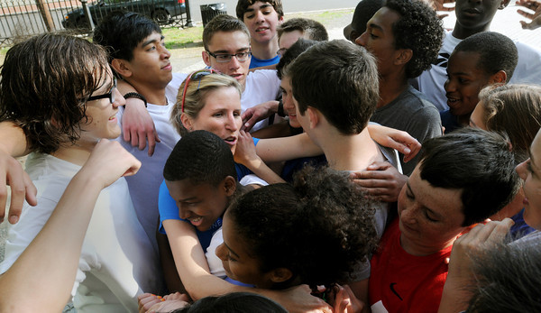 "Salem:<br /> Salem Charter School teacher Allison Rickenbach gets hugged by the school's track team after her run. Allison was 4/10th of a mile away from finishing the Boston Marathon last month before the race was halted by the explosions. Friday afternoon, she ""finished"" the marathon by running her final distance around the Salem Common, along with students from the Charter school's track team.<br /> Photo by Ken Yuszkus/Salem News, Friday June 10, 2013."