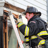 Salem: Salem Fire Lieutenant Bob Cook peers into the front corner of Walyo's Variety located at 20 Essex St. in Salem on Friday afternoon after a small fire broke out. David Le/Salem News