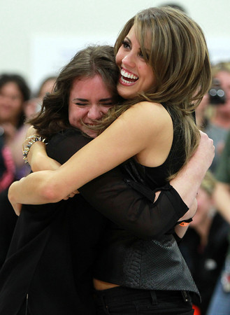 Beverly: American Idol Finalist Angie Miller, right, hugs her best friend and current Beverly High School senior Lydia Hester, 17, after presenting her with 4 tickets to the next live American Idol show. Miller talked with a large group of Centerville Elementary School students about the importance of having a best friend, just before presenting Hester with the tickets and a big hug. David Le/Salem News