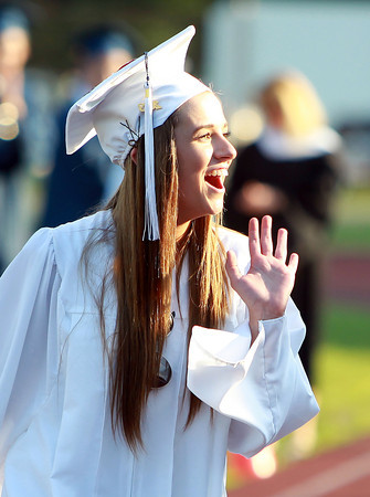 Peabody: Peabody graduate Micayla Caruso waves to her family as she walks across the field to receive her diploma during Graduation on Friday evening. David Le/Salem News
