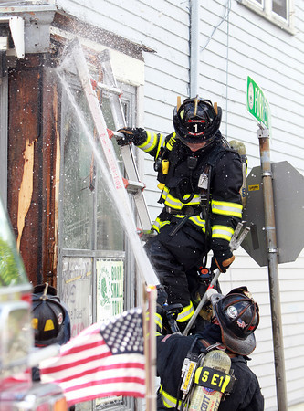 Salem: A couple Salem firefighters spray water on the front corner of Walyo's Variety located at 20 Essex St. in Salem on Friday afternoon after a small fire broke out. David Le/Salem News