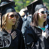 Wenham: Gordon College graduates Katie Messina and Ashleigh Long hold their hands over their hearts while singing the Star Spangled Banner. David Le/Salem News