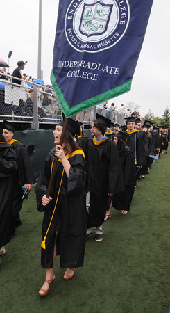 Beverly:<br /> Graduate Caroline Pope carries a banner while leading the graduates into the stadium at Endicott College's graduation ceremony. <br /> Photo by Ken Yuszkus/Salem News, Friday May 24, 2013.
