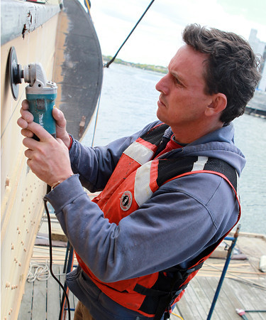 Salem: John Linsley, of FJ Dion Yacht Yard, uses a sander to repair the hull of the Friendship. David Le/Salem News