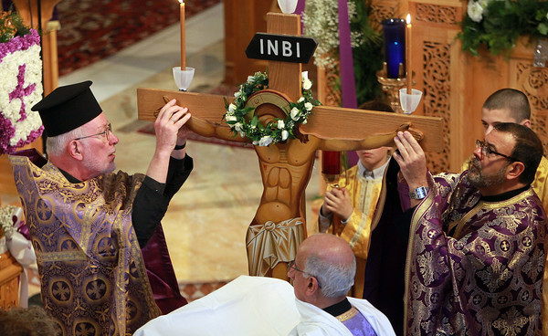 Peabody: Reverend Andrew Demotses, left, and Reverend Christopher Foustoukos, right, take Jesus Christ off the cross during a Good Friday ceremony at St. Vasilios Greek Orthodox Church on Friday afternoon. David Le/Salem News