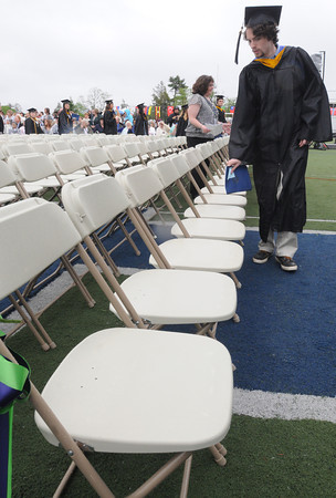 Beverly:<br /> Graduate Devin Lee finds his chair in the front row during the processional at the stadium during Endicott College's graduation ceremony. <br /> Photo by Ken Yuszkus/Salem News, Friday May 24, 2013.