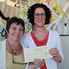 "Beverly: Lorna Lampert, of Beverly, is handed a gift card for the Beverly Bootstraps Thrift Shop by Manager Jackie Hersey, left. Lampert  won the Beverly Bootstraps ""Renew the Old"" competition, where pieces of furniture from the thrift shop were refurbished and entered into a competition judged by a panel of local judges. David Le/Salem News"