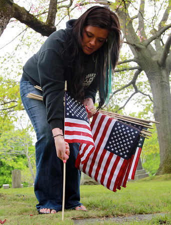 Beverly: Lauren Swift, of Middleton, places a flag in front of a veteran's grave in Walnut Grove Cemetery on Wednesday afternoon. David Le/Salem News