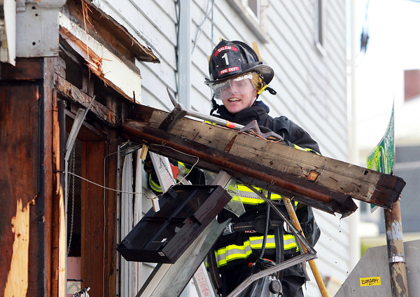 Salem: Salem firefighter Matt Keane uses a crowbar to take off the front corner of Walyo's Variety located at 20 Essex St. in Salem on Friday afternoon after a small fire broke out. David Le/Salem News