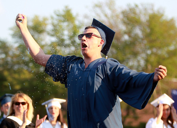 Peabody: Peabody graduate Allen Pereira pumps his fists in the air and shoots a can of silly string in the air as his name is called to receive his diploma on Friday evening. David Le/Salem News