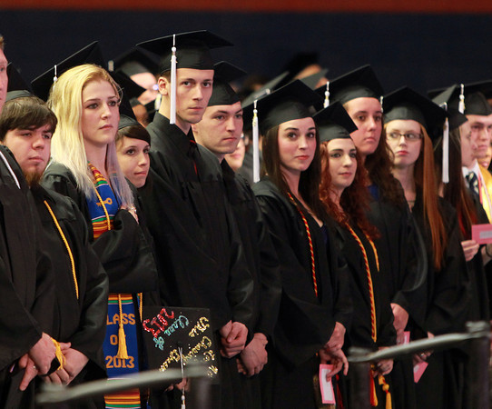 Salem: Salem State University graduates stand and listen to classmate Jenney Richards sing the National Anthem on Saturday afternoon. David Le/Salem News