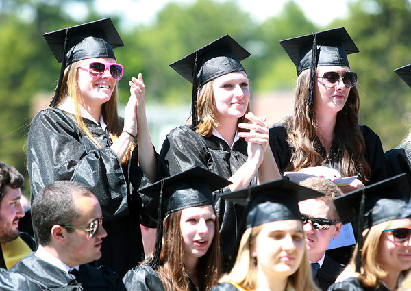 Wenham: Gordon College graduates Megan Grant, Sarah Flanders, and Allison Faber stand up and cheer on classmates as they cross the stage and receive their diplomas on Saturday morning. David Le/Salem News