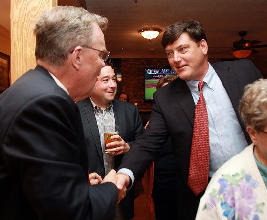 Danvers: Former Danvers Selectman Keith Lucy, right, shakes hands with newly-elected David Mills, left, and congratulates him on the win inside Timothy's Grill on Route 1 in Danvers, after the unofficial precinct numbers came in. David Le/Staff Photo