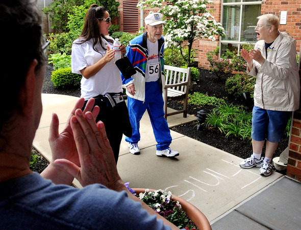 Peabody:<br /> Ninety-six year old resident Jack Borteck crosses the finish line with employee Carmen Filetto as Nancy Trott, left, and Barabara Wroblewski, right, cheer him on during the 12th annual Brooksby Village Marathon. He was one of many finishers.<br /> Photo by Ken Yuszkus, Wednesday May 29, 2013.
