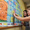 "Beverly:<br /> Fifth-grade Student Council members Abby Brauninger, left, and Leilani Jones prepare to attach ""Dog Paws"" on the ""Paws for a Cause"" display in the Cove Elementary School hallway. Cove Elementary School is trying to raise $9,500 to buy a therapeutic service dog to support special education students at the school. Students and families can purchase a ""Dog Paw"" for $1 as part of the fund-raising campaign.<br /> Photo by Ken Yuszkus/Salem News,  Wednesday May 22, 2013."
