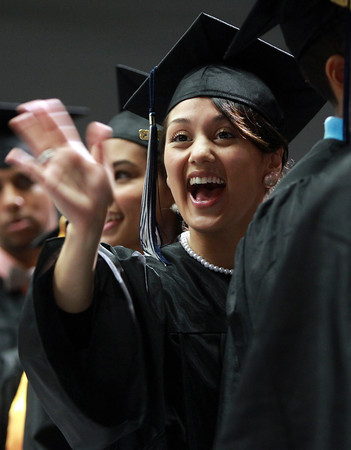 Salem: North Shore Community College graduate Brianna Ramirez, of Salem, smiles and waves to her family while marching into Commencement on Thursday evening. David Le/Salem News
