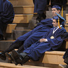 Danvers:<br /> Eric O'Connor of Andover, left, and Harrison Simbliaris of Marblehead stretch out as they wait for their names to be called to line up in the Memorial Gymnasium before the procession starts for the St. John's Prep graduation.<br /> Photo by Ken Yuszkus/Salem News,  Sunday May 19, 2013.