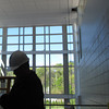 Wearing a hard hat, Selectman Dan Bennett, from left, and School Committee members Connie Pawlak and Eric Crane are silhouetted by light coming from a new three-story entrance atrium of the academic wing on the west side of Danvers High. The entrance, which leads to the main student parking lot, is part of the nearly $71 million construction project.<br /> Ethan Forman/staff photographer