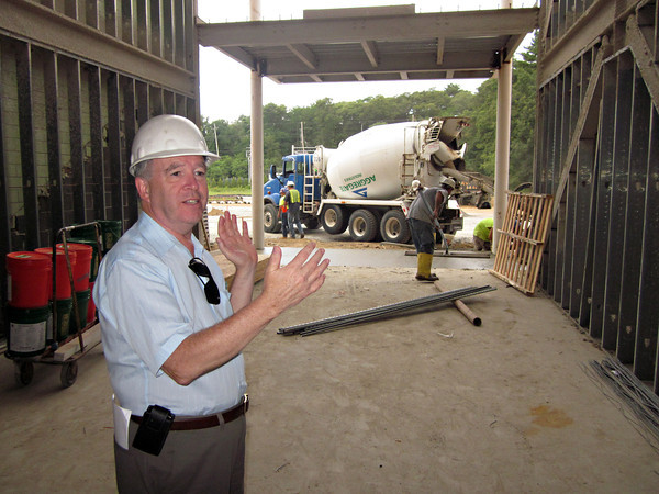 DANVERS: Project Manager Paul Griffin, the principal of Construction Monitoring Services Inc. of Marlborough, shows the new entrance to the high school's academic wing. In the background, workers pour a new cement floor. Photo by Ethan Forman