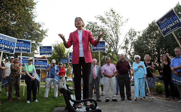 U.S. Senate candidate Elizabeth Warren stands on a bench and addresses a large group of her supporters in Veterans Park in Beverly on Thursday evening. David Le/Staff Photo