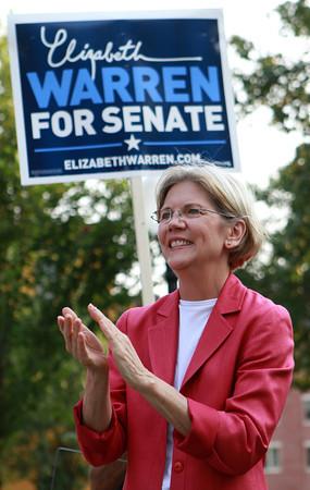 U.S. Senate candidate Elizabeth Warren applauds Beverly Mayor Bill Scanlon at Veterans Park in downtown Beverly on Thursday evening. David Le/Staff Photo