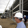 Aug. 5, 2011: Wearing a hardhat, Holten Richmond Middle School Principal Michael Cali, who is overseeing the Danvers High renovation project for the school department, watches as a load of roof insulation tiles is hoisted to the roof of the new lobby to the Danvers High auditorium. Cali stands adjacent to double beams that will form the school's new facade. <br /> Ethan Forman/Staff photographer