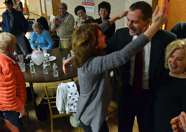 Beverly: Jerry Parisella celebrates winning the Beverly state representative election.  His sister Karen Parisella, left, hugs him as he comes into the Italian Community Center with his wife Lisa, right.  photo by Mark Teiwes / Salem News