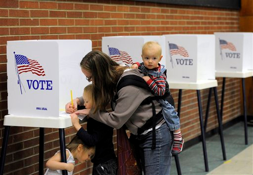 Mah-rya Proper, 38, has her son Augie Proper, 5, left, help fill-out her ballot with her other son Elisha Proper, 1, right, and daughter Eliana Proper, 3, bottom left, plays at the Mi Casa Resource Center in Denver, Colo., on Tuesday, Nov. 2, 2010. American voters go the polls for the mid-term elections. (AP Photo/Chris Schneider)