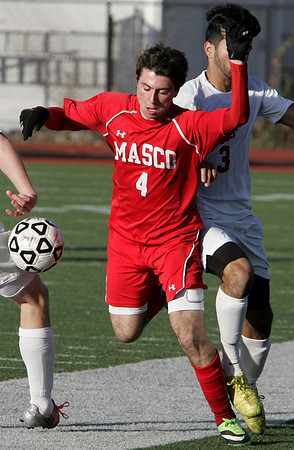 Lynn:<br /> Masco's Paul Criscione, left, is heading for the ground as North Andover's Sina Samali comes from behind while they go after the loose ball during the North Andover vs. Masco boys soccer North final at Manning Field in Lynn.<br /> Photo by Ken Yuszkus / The Salem News, Monday, November 11, 2013.