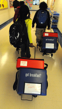 Salem:<br /> Students transport the carts containing their classroom's breakfasts toward their classrooms at the Carlton Elementary School. The Salem Public Schools have started a grant-funded breakfast in the classroom program.<br /> Photo by Ken Yuszkus / The Salem News, Friday, November 22, 2013.