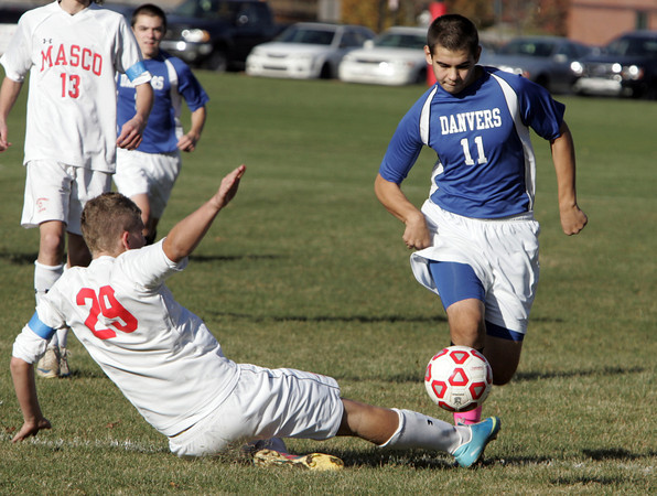 Topsfield:<br /> Masco's Alex Spaulding slides to kick the ball as Danvers' Nikolay Sakhin attacks during the Danvers at Masconomet boys soccer in Division 2 North quarterfinals.<br /> Photo by Ken Yuszkus / The Salem News, Tuesday, November 5, 2013.