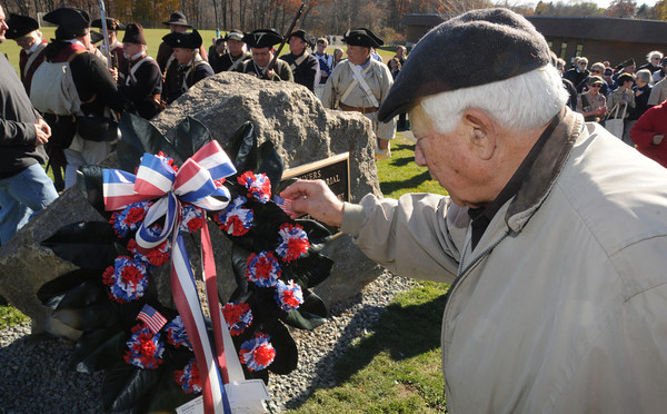 Danvers:<br /> Korean veteran Larry Raimondi places a small flag on the wreath near the new memorial at the conclusion of the Danvers Veterans Council dedication of the memorial at the Veterans Memorial fields at the Thorpe School.<br /> Photo by Ken Yuszkus / The Salem News, Monday, November 11, 2013.