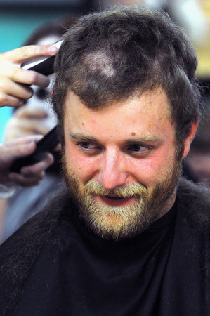 Beverly:<br /> Patches of hair are carved out of 4th grade teacher Charlie Juliand hair as he gets a haircut from Annie Curtin in front of students and faculty of St. Mary School.<br /> Photo by Ken Yuszkus / The Salem News, Monday, November 18, 2013.