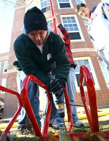 Salem: Ed Burge uses a drill to assemble a jungle gym behind the Saltonstall School in Salem on Saturday morning. A bunch of volunteers, mostly parents and teachers, worked all day Saturday to complete a playground which was not in the renovation plans after it was burned down in 2010. David Le/Salem News