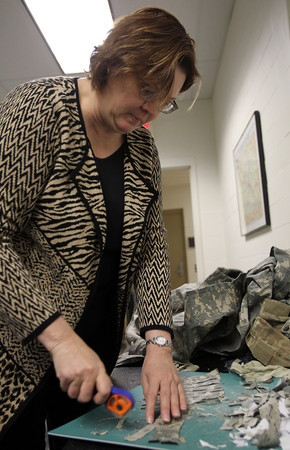 Salem: Vickie Morrison, an Air Force Veteran and current Salem State University faculty member, cuts military uniforms into small squares before they are turned into a pulp used to make paper. The Combat Paper Project is a nationwide art project where veterans turn their uniforms into paper as a way to express their thoughts and experiences of serving in the military. David Le/Salem News