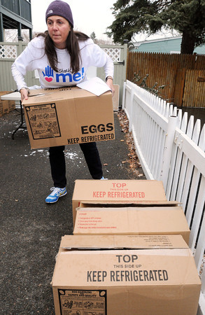 "Salem:<br /> Melanie McKinnon carries a box full of food toward a truck which will transport it to a needy family. Melanie runs a charity called  ""It Starts With Me!"". Tuesday they distributed turkey and all the supplies to 117 families in Salem and neighboring towns. <br />  Photo by Ken Yuszkus / The Salem News, Tuesday, November 26, 2013."