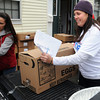"Salem:<br /> Melanie McKinnon, right, slides a box full of food into a pickup truck bed which will transport it and other boxes to needy families. Melanie runs a charity called  ""It Starts With Me!"". Tuesday they distributed turkey and all the supplies to 117 families in Salem and neighboring towns. <br />  Photo by Ken Yuszkus / The Salem News, Tuesday, November 26, 2013."