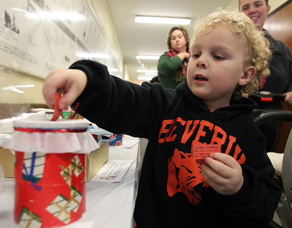 Beverly: Four-year-old Cameron Tremblay, of Beverly, drops a raffle ticket into a jar at the annual Beverly Holiday Fair at the First Baptist Church on Saturday evening. David Le/Salem News