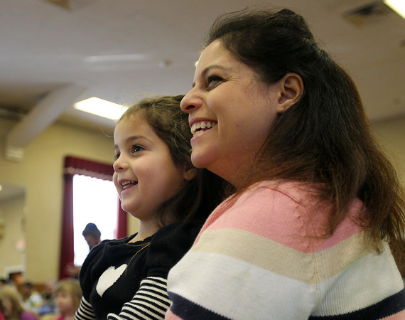 Peabody: Greta Taglieri and her daughter Aliya, 4, of Beverly, laugh while watching magician Eddie Gardner at the first Hannukah celebration held at the Knights of Colombus on Main St. in Peabody on Friday morning. David Le/Salem News