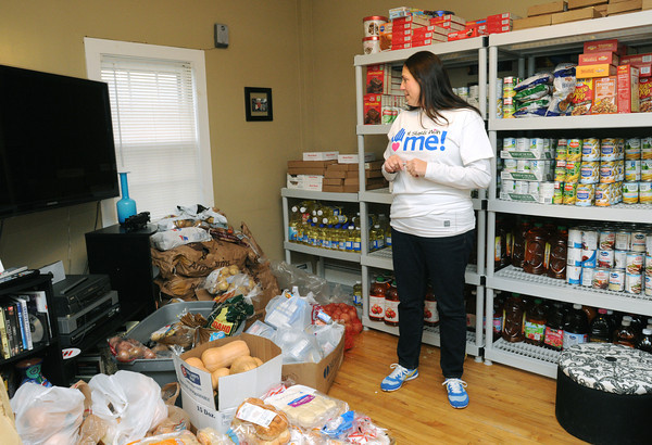 "Salem:<br /> Melanie McKinnon looks over the large quantity of food covering her livingroom. Melanie runs a charity called  ""It Starts With Me!"". Tuesday they distributed turkey and all the supplies to 117 families in Salem and neighboring towns. <br />  Photo by Ken Yuszkus / The Salem News, Tuesday, November 26, 2013."