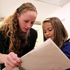 Beverly: Emily Pallin, founder and Art Director of Let's Get Creative in Beverly, looks over some artwork done by seven-year-old Ellie Corbett, of Beverly, during an after school class on Thursday evening. David Le/Salem News