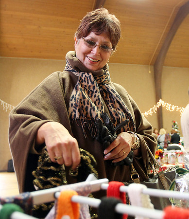 Beverly: Carmen Amenta, of Peabody, looks at some scarves at the annual Beverly Holiday Fair on Saturday morning. David Le/Salem News