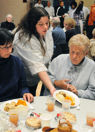 Salem:<br /> Abby Seybold, from culinary arts, center, serves turkey dinners to Sandra Moore, left, and Carol Turner, right, at the Senior Citizens Thanksgiving Lunch held at the Salem High School auditorium.<br /> Photo by Ken Yuszkus / The Salem News, Thursday, November 21, 2013.