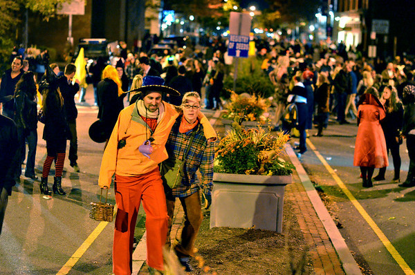 Saturday night scenes Halloween weekend in Salem:  Phil McKenna, left, wears a tea party costume walking with Rachel Parrish, both of Cambridge, back to the train station along Washington Street at the end of the night's festivities.   photo by Mark Teiwes / Salem News.